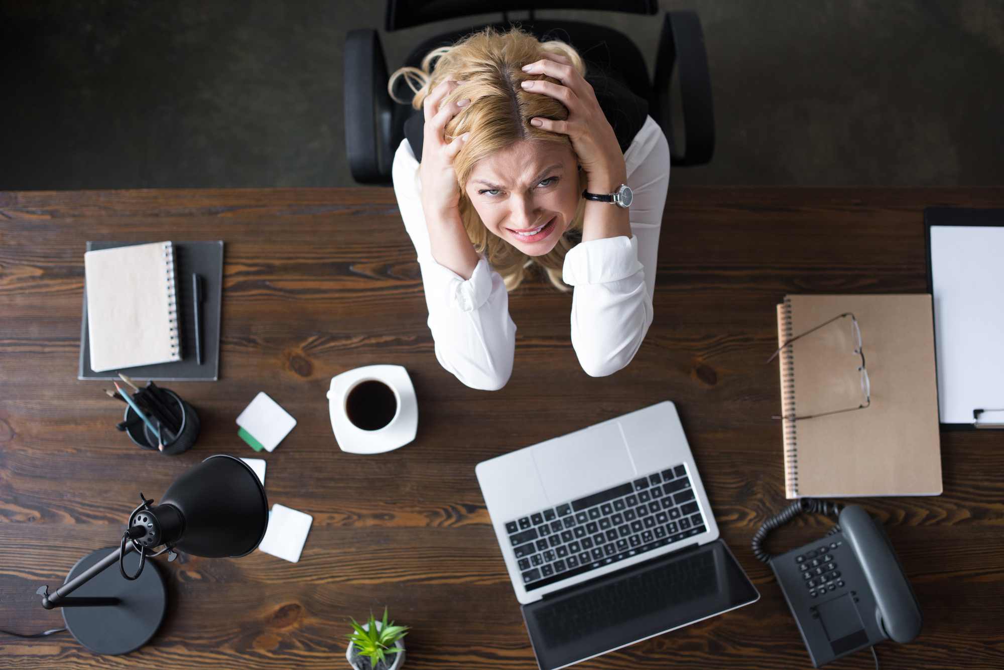 Overhead view of stressed businesswoman touching head with hands and looking at camera in office