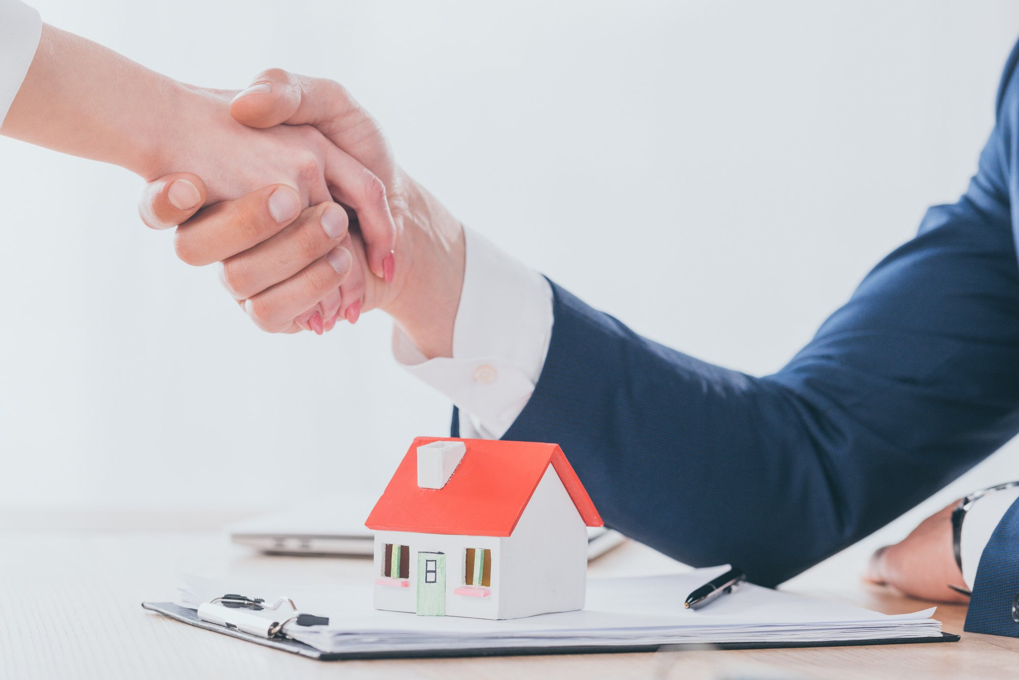 Partial view of realtor shaking hands with customer near house model on tabletop
