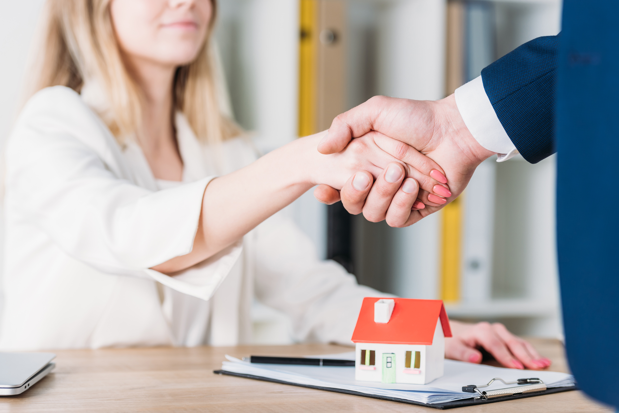 Partial view of smiling woman shaking hands with realtor near house model on table