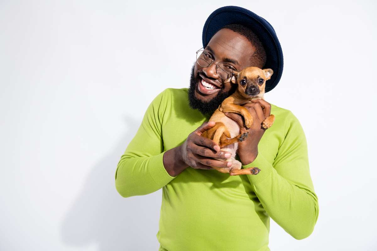 Portrait of cheerful guy hugging his toy terrier wearing eyeglasses eyewear isolated over white background (R) (S)