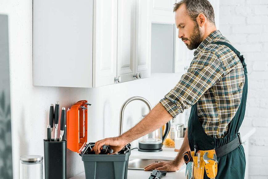 Side view of handsome plumber taking tools from toolbox in kitchen (R) (S)